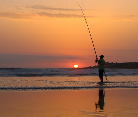 Man_fishing_at_sunset_in_Mehdia_beach